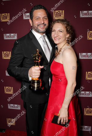 Alexander Dinelaris, left, and Nyla Mabro are seen with his award for best original screenplay at the 20th Century Fox & Fox Searchlight Oscar Party at BOA Steakhouse, in West Hollywood, Calif