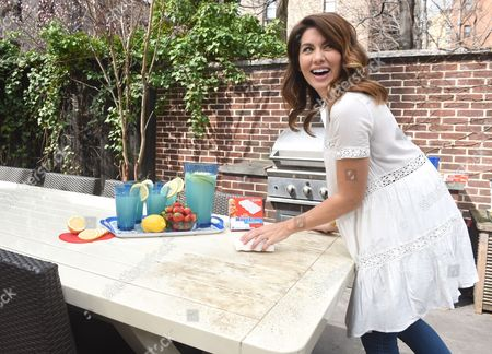 Stock Image of In this photo released, design expertJillian Harris uses aMr. CleanMagic Eraser to remove winter buildup from patio furniture while on the set of the Mr. Clean Dirty Little Secret video shoot in New York.Â