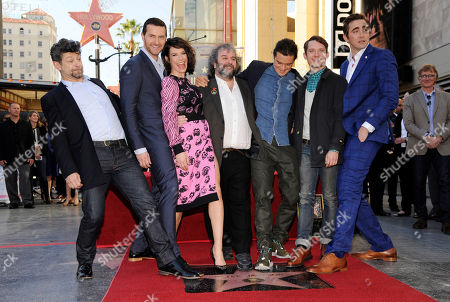 """Peter Jackson, fourth from left, director, co-writer and producer of the film trilogies """"The Lord of the Rings"""" and """"The Hobbit,"""" poses with actors, left to right, Andy Serkis, Richard Armitage, Evangeline Lilly, Orlando Bloom, Elijah Wood and Lee Pace during a ceremony honoring Jackson with a star on the Hollywood Walk of Fame, in Los Angeles"""