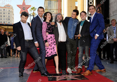 """Director/producer/screenwriter Peter Jackson, fourth from left, poses with actors, left to right, Andy Serkis, Richard Armitage, Evangeline Lilly, Orlando Bloom, Elijah Wood and Lee Pace during a ceremony honoring him with a star on the Hollywood Walk of Fame, in Los Angeles. Jackson is director, co-writer and producer of the film trilogies """"The Lord of the Rings"""" and """"The Hobbit"""