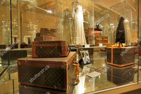 """1959 Brettes Hat/Shoe Trunk & Vanity Case, 1997 Cruiser Bag. A 1959 Brettes Hat/Shoe Trunk & Vanity Case, foreground left, that once belonged to Lauren Bacall, and a 1997 Cruiser Bag, foreground right, that once belonged to Jane Fonda, right, are displayed as part of the """"Volez, Voguez, Voyagez,"""" Louis Vuitton exhibit, in the former American Stock Exchange building, in New York Financial District, . The luxury French brand, founded in the mid-19th century, is telling its story with a free, museum-like exhibition of artifacts, products and immersive displays. The exhibition is on view at the American Stock Exchange Building in Lower Manhattan until Jan. 7"""