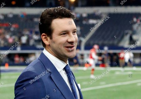 CBS football analyst Tony Romo walks across the field during warm ups before an NFL football game between the Kansas City Chiefs and Dallas Cowboys, in Arlington, Texas