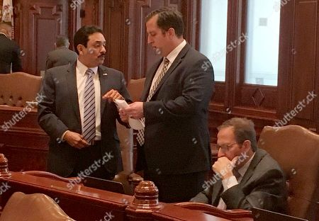 Stock Image of Democratic Senators Tony Munoz D-Chicago, left, and Michael Hastings D-Tinley Park, speak on the floor of the Illinois Senate as Senator Ira Silverstien, D-Chicago, sits nearby, in Springfield, Ill. The Senate voted to expand power of the newly appointed inspector general to allow her to investigate existing complaints, including one filed last November by legislative activist Denise Rotheimer against Silverstein