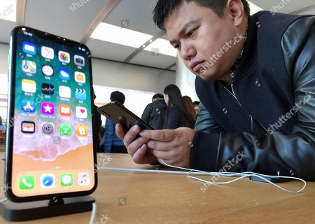 A shopper looks at the latest iPhone X from U.S. tech giant Apple at a retail store in Beijing, China. After a brief truce with China to cooperate over North Korea, U.S. President Donald Trump visits Beijing this week amid mounting U.S. trade complaints, with limited prospects for progress on market access, technology policy and other sore points. The strains between the world's two biggest economies are fueling anxiety among global companies and advocates of free trade that they could retreat into protectionism, dragging down growth