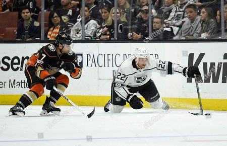 Trevor Lewis, Andrew Cogliano. Los Angeles Kings center Trevor Lewis, right, dives for the puck while under pressure from Anaheim Ducks left wing Andrew Cogliano during the third period of an NHL hockey game, in Anaheim, Calif. The Kings won 4-3 in overtime