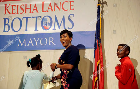 Atlanta city councilwoman and mayoral candidate Keisha Lance Bottoms steps onstage with her children Lennox, 7, left, and Langston, 9, to speak at an election night party in Atlanta, . Nearly a dozen candidates are competing to succeed term-limited Atlanta Mayor Kasim Reed. With so many contenders running, it's a safe bet that some of these elections won't be settled Tuesday. For any race in which no candidate wins more than 50 percent of the vote, the top two finishers will return for a runoff election Dec. 5