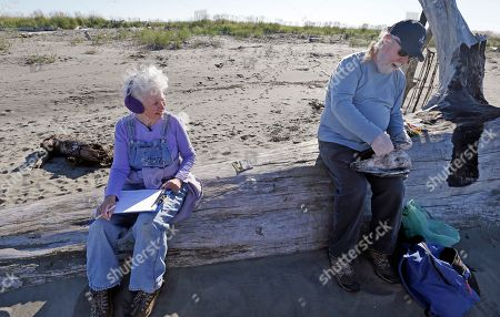 Barb Patton, left, records information as her husband Mike Patton examines a dead bird as part of a citizen patrol surveying dead birds that wash ashore on beaches along the U.S. West Coast, in Ocean Shores, Wash. A long-running citizen monitoring program at the University of Washington is tracking dead seabirds as an indicator of the health of the coastal environment