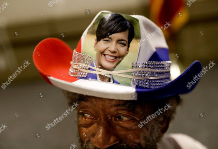 Charles Doyle wears a hat decorated with an image of Atlanta city councilwoman and mayoral candidate Keisha Lance Bottoms as she speaks at an election night party in Atlanta, early . Nearly a dozen candidates are competing to succeed term-limited Atlanta Mayor Kasim Reed. With so many contenders running, it's a safe bet that some of these elections won't be settled Tuesday. For any race in which no candidate wins more than 50 percent of the vote, the top two finishers will return for a runoff election Dec. 5