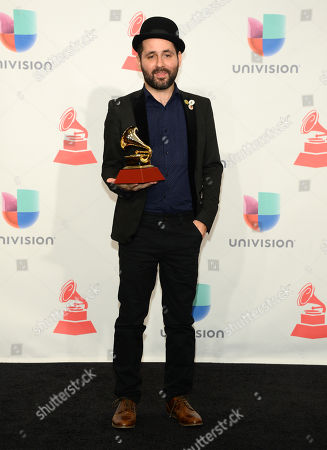 """Visitante, of Calle 13, poses in the press room with the award for best short form music video for """"Ojos Color Sol,"""" at the 16th annual Latin Grammy Awards at the MGM Grand Garden Arena, in Las Vegas"""