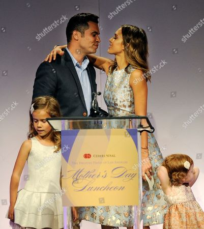 Stock Image of Actress Jessica Alba kisses her husband Cash Warren as she accepts her Mother of the Year award at the 85th Helping Hand of Los Angeles Mother's Day Luncheon, Friday, May 9. 2014 in Beverly Hills, Calif. Looking on are their daughters Honor Marie, left, and Haven Garner