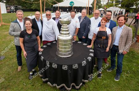 Stock Photo of Tim Love, Stephanie Izard, Jim Clark, Jimmy Bannos Sr, Paul DeShaw, Graham Elliot, Larry O'Brien, Tony Mantuano, Mindy Segal, Danny Wirtz and Charlie Jones pose with the Stanley Cup at the Feast Under the Stars event during the Chicago Food + Wine Festival, in Chicago