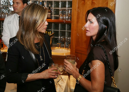 Jennifer Aniston, left, and Courteney Cox are seen as Justin Theroux and Dan Peres celebrate the August issue of DETAILS at The Sunset Tower Hotel on in West Hollywood, Calif