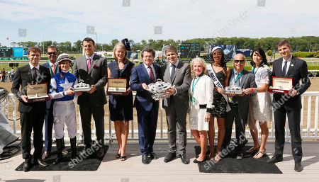 Robert Masterson, owner, center, accepts a Longines Classic Conquest timepiece from Jennifer Judkins, center left, and a trophy from Juan Carlos Capelli of Longines, center right, after jockey Julien Leparoux wins the Longines Just a Game race on Tepin, at the 147th Belmont Stakes at Belmont Park Race Track, on in Elmont, N.Y