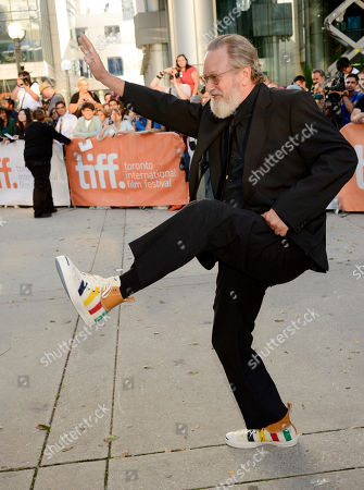 """Stock Photo of Jeremiah Chechik, director of """"The Right Kind of Wrong,"""" shows off his sneakers to photographers at the premiere of the film on day 8 of the 2013 Toronto International Film Festival at Roy Thomson Hall, in Toronto"""