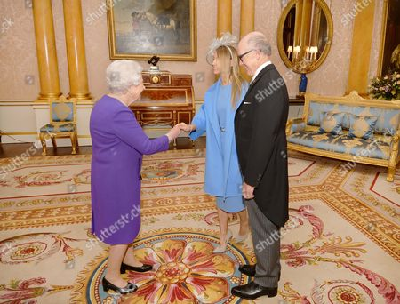 Queen Elizabeth II shakes hands with Mrs Suzanne Johnson, the wife of the US Ambassador to the UK, Woody Johnson (right), after he presented his Letters of Credence at a private audience at Buckingham Palace