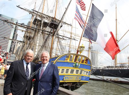 """Craig Stapelton former US Ambassador for France and Christophe Navarre President and CEO of Moet Hennessy poses for a photo while the Hermione is seen behind them docked at the """"Hennessy 250 Celebrates the Hermione's arrival in New York Harbor"""" at Pier 15, in New York"""