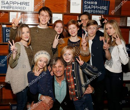 "Actor Viggo Mortensen is surrounded by cast members from ""Captain Fantastic,"" back from left to right, Samantha Isler, George MacKay, Annalise Basso, Trin Miller, director Matt Ross, Nicholas Hamilton and Erin Moriarty, front left, Shree Crooks and Charlie Shotwell, front right, at the Indiewire Photo Studio at Chase Sapphire on Main, on in Park City, Utah"