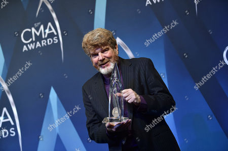 """Singer-songwriter Mac McAnally poses with the award for """"Musician of the Year"""" in the press room at the 51st annual CMA Awards at the Bridgestone Arena, in Nashville, Tenn"""
