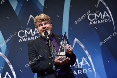 Singer-songwriter Mac McAnally poses with the award for musician of the year in the press room at the 51st annual CMA Awards at the Bridgestone Arena, in Nashville, Tenn