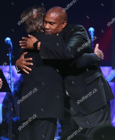 Tavis Smiley, right, hugs founder award winner John Mellencamp at the 33rd annual ASCAP Pop Music Awards at the Dolby Ballroom, in Los Angeles