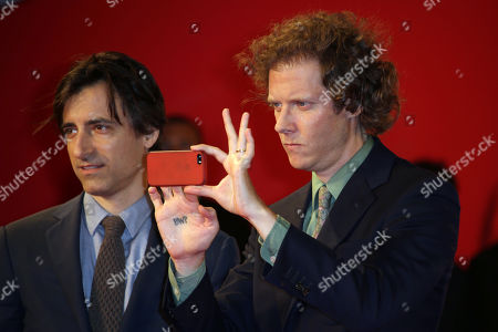 Jake Paltrow, right, takes a photograph with his phone as he poses for photographers with Noah Baumbach upon arrival on the red carpet for the documentary film De Palma, prior to Brian De Palma collecting the Glory to the Filmmaker Award during the 72nd edition of the Venice Film Festival in Venice, Italy