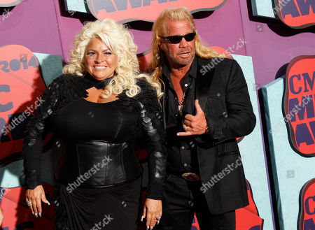 "Beth Chapman, left, and Duane Chapman arrive at the CMT Music Awards at Bridgestone Arena, in Nashville, Tenn. Hawaii's attorney general says ""Dog the Bounty Hunter"" reality TV star Duane ""Dog"" Chapman's bail bonds business owes the state $35,000. Attorney General Doug Chin says, his office is suing Da Kine Bail Bonds for money it promised to pay when the company's clients skipped court"