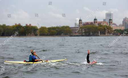 """Martin Strel passes Ellis Island as he swims from the Statue of Liberty to Downtown Manhattan's North Cove Marina, in New York. On March 22, 2016, World Water Day, Strel will commence his """"Strel World Swim"""" through 107 countries in approximately 450 days as a means of spreading clean water awareness"""