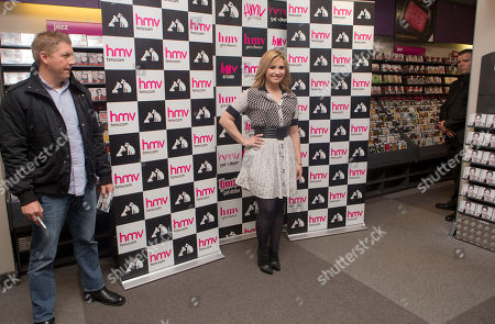Demi Levato is flanked by two security guards as she arrives at a HMV store in Oxford Street, central London, before the U.S singer meets fans and promotes her album