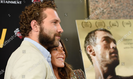 "Actor Jai Courtney, left, and Vashti Whitfield, widow of actor Andy Whitfield, pose together at the premiere of the film ""Be Here Now (The Andy Whitfield Story,"" at the UTA Theater, in Beverly Hills, Calif"