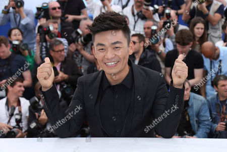 Actor Baoqiang Wang gestures to photographers during a photo call for the film Stranger by the Lake at the 66th international film festival, in Cannes, southern France