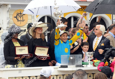 Zaneta Sampson, left, and Jennifer Judkins, second left, of Longines, get ready to present Longines Conquest Classic timepieces as jockey Victor Espinoza and the American Pharoah team celebrate their win at the 140th Preakness Stakes and the second leg of the Triple Crown, in Baltimore, Md. Longines, the Swiss watch manufacturer known for its elegant timepieces, is the Official Watch and Timekeeper of the 140th annual Preakness Stakes and the Triple Crown