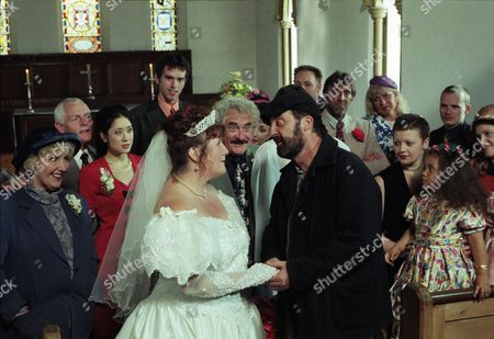 Stock Image of Ep 2254 Wednesday 10th September 1997 Betty tells a reluctant Zak he's got to go to the church and stop the wedding between Albert and Lisa otherwise he and Lisa may regret it for the rest of their lives. Dashing to the church Zak professes his love for Lisa and the whole congregation cheers. Reverend Ashley decides to bless the relationship outside - With Betty Eagleton, as played by Paula Tilbrook ; Eric Pollard, as played by Christopher Chittell ; Dee de la Cruz, as played by Claudia Malkovich; Lisa Clegg, as played by Jane Cox ; Zak Dingle, as played by Steve Halliwell ; Albert Dingle, as played by Bobby Knutt ; Marlon Dingle, as played by Mark Charnock ; Rev Ashley Thomas, as played by John Middleton.