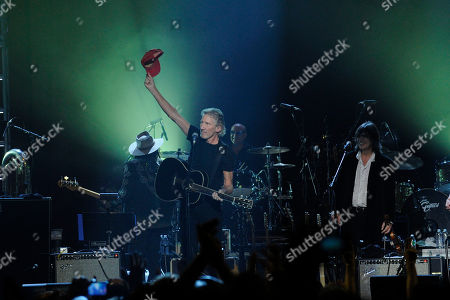 Stock Photo of Musician Roger Waters holds up a hat given to him by the late Levon Helm while performing onstage at the Love for Levon Concert, in East Rutherford, New Jersey