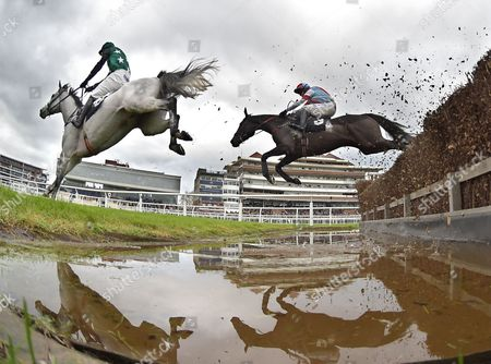 (R) Willie Boy (Liam Treadwell) takes the water before going on to win The Dawnus Handicap Steeple Chase with (L) Greybougg (Danny Cook) alongside.