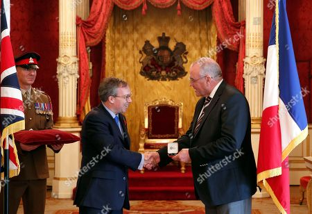 British ambassador to France, Lord Ed Llewellyn, left, awards Chris Norman of the Queen's Commendation for Bravery, in Paris, . Norman and three Americans overpowered an Islamic extremist with an assault rifle who tried to open fire on a Thalys train traveling from Amsterdam to Paris In August 2015