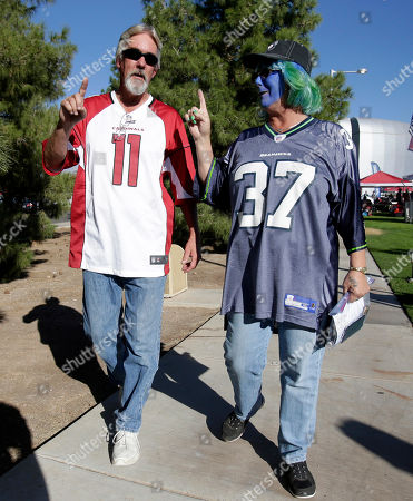 Arizona Cardinals fan Jeff Hall and Seattle Seahawks fan Deborah Cook arrive prior to an NFL football game, in Glendale, Ariz