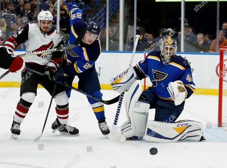 Arizona Coyotes' Zac Rinaldo, left, and St. Louis Blues goalie Carter Hutton, right, and Blues' Vince Dunn watch the puck during the first period of an NHL hockey game, in St. Louis