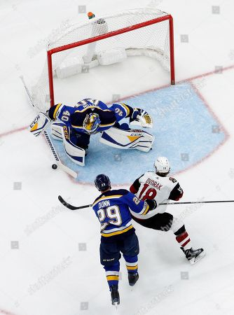 St. Louis Blues goalie Carter Hutton (40) rejects an attempt by Arizona Coyotes' Christian Dvorak (18) as Blues' Vince Dunn (29) defends during the first period of an NHL hockey game, in St. Louis