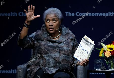 Former Democratic National Committee chair Donna Brazile holds a copy of her book Hacks, detailing the hacking of the DNC, during a meeting of The Commonwealth Club, in San Francisco