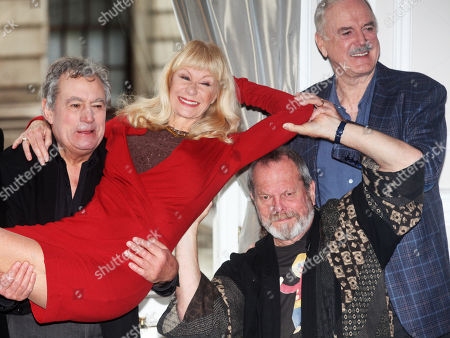Terry Jones, lifts Carol Cleveland as Terry Gilliam and John Cleese of the comedy troop Monty Python help at a photo call, on in London. They are reuniting for a project
