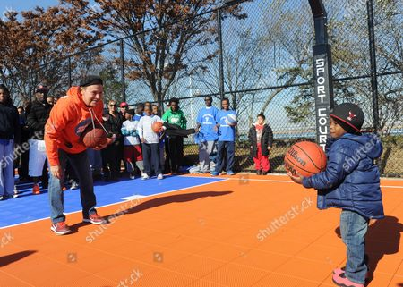 Actor and comedian Billy Crystal plays a game of basketball with Zion Johnson, 2, of Long Beach, at the opening ceremony for two new DreamCourts, in Long Beach, N.Y. The courts were constructed and opened today, one-year post Hurricane Sandy, thanks to the Nancy Lieberman Foundation, WorldVentures Foundation and Billy and Janice Crystal