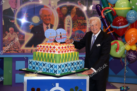 """This photo shows Bob Barker posing on the set of """"The Price is Right"""" with a cake celebrating his 90th birthday at CBS Studios in Los Angeles. The veteran game show host, at the helm of The Price is Right from 1972 to 2007, was invited back by current host Drew Carey on Thursday, Dec. 12, to celebrate the milestone birthday"""