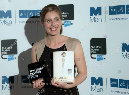 New Zealand author Eleanor Catton poses after being announced the winner of the Man Booker Prize for Fiction, holding her prize and her book for the photographers, in central London, . Catton won the 50,000 pounds ($80,000) prize with her book 'The Luminaries