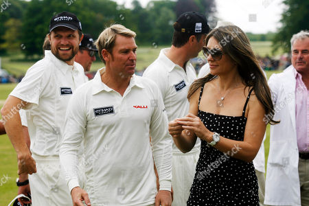 """Stock Photo of Elizabeth Hurley and Shane Warne walk over to the official coin toss with her son Damien at the """"Cricket for Kids"""" charity match she is hosting between England and Australia at the Cirencester Tennis Club in Cirencester in England on"""