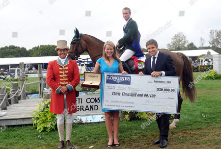 Juan-Carlos Capelli and Jennifer Judkins, of Longines, present Richie Moloney, of Ireland, with a Longines timepiece and a $30,000 prize after Moloney won the inaugural Longines Rider Challenge during the Hampton Classic, in Bridgehampton, NY. Longines is the official watch and timekeeper of the 38th annual Hampton Classic Horse Show