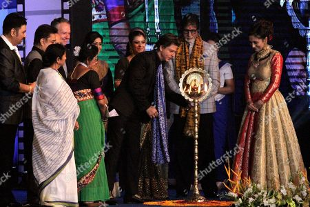 Bollywood actor Shahrukh Khan lights the lamp, as Amitabh Bachchan, second right, Chief Minister of West Bengal state Mamata Banerjee, wearing white, and other Bollywood personalities watch at the inauguration of 23rd Kolkata International Film Festival in Kolkata, India, . The festival will continue till Nov. 17