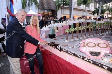 IMAGE DISTRIBUTED FOR THE RODEO DRIVE COMMITTEE - Rodeo Drive Committee President Jim Jahant, left, and Beverly Hills Mayor Lili Bosse cut a slice of a massive 15 foot by 20 foot cake presented by the Luxe Hotel Rodeo Drive and Guittard Chocolate at the BH100 Centennial Block Party on Rodeo Drive, in Beverly Hills, Calif. The block party also featured carnival rides, games, and fireworks in celebration of the city's 100th birthday