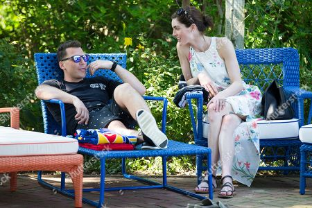 Former hockey player Sean Avery, left, and model Hilary Rhoda relax by the pool at the Solid & Striped BBQ & Pool Party, in Southampton, N.Y