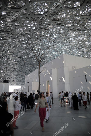 People walk under the dome of the Louvre Abu Dhabi museum during its official public opening, in Abu Dhabi, UAE, 11 November 2017. The dome was designed by French architect Jean Nouvel.