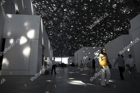 People walk as sunlight bursts through a randomly perforated double dome of the Louvre Abu Dhabi museum during its official public opening, in Abu Dhabi, UAE, 11 November 2017. The dome was designed by French architect Jean Nouvel.